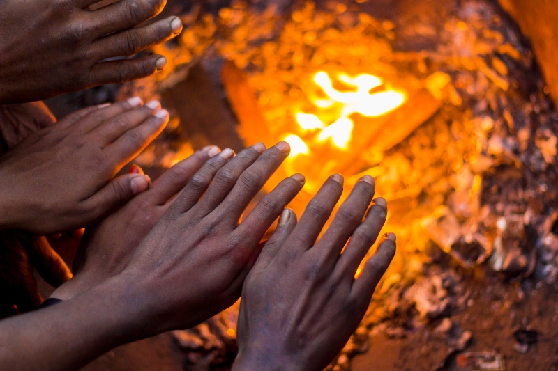 People warming hands on the fire in india